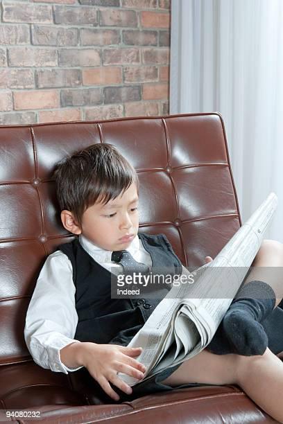 Boy dressed as a businessman reads a newspaper
