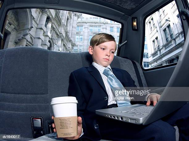 Boy Dressed as a Businessman, Sitting in a Taxi Using a Laptop Computer
