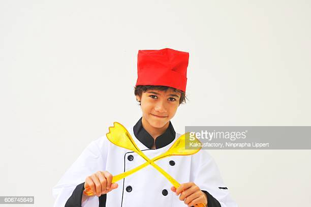 A boy dressed as a chef holding salad servers