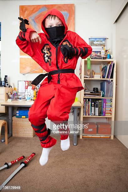 Boy dressed as a ninja jumping
