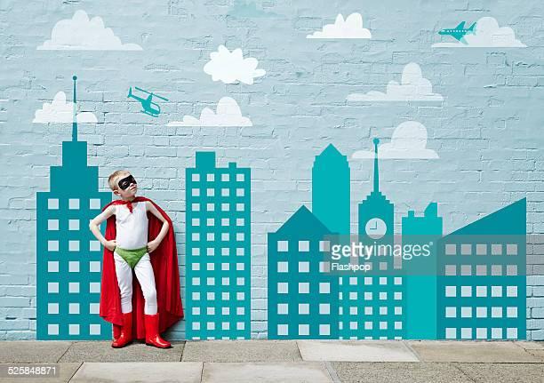Boy dressed as a superhero. Cartoon city skyline