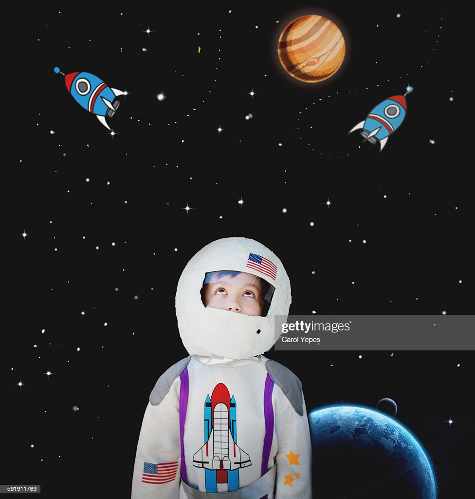 Boy dressed as astronaut.Cartoon in background : Stock Photo