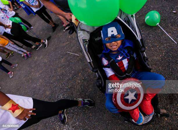 A boy dressed as 'Capitan America' rests in his stroller during the '5K Heroes with True Battles' in support of children with cancer in Managua on...