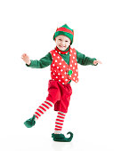 * Motion Blur. A happy, joyful, smiling boy, dressed as a Christmas elf, dances a gleeful jig.