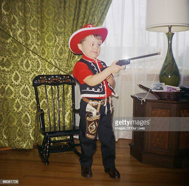 Boy dressed as cowboy aiming toy gun