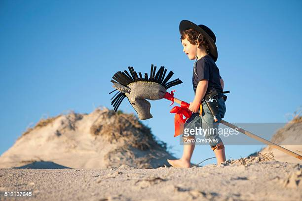 Boy dressed as cowboy with hobby horse in sand dunes
