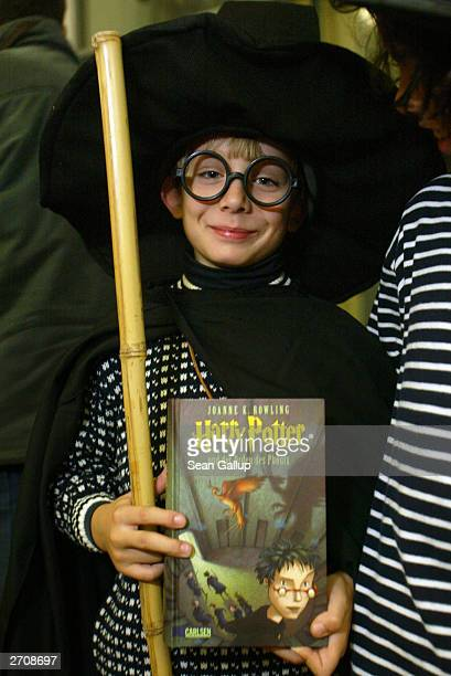 A boy dressed as kid wizard Harry Potter holds his justpurchased copy of the Germanlanguage edition of 'Harry Potter and the Order of the Phoenix'...