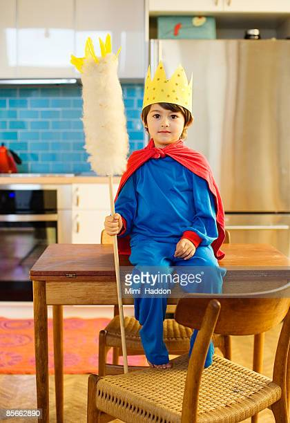 Boy dressed as king in his kitchen