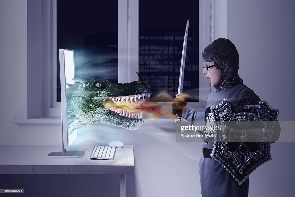 Boy dressed as knight confronts a computer dragon : Stock Photo
