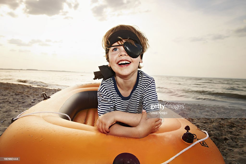 Boy (4 - 5 years) dressed as pirate on beach : Foto stock