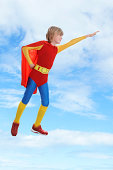 Boy dressed as superhero flying against cloudy sky