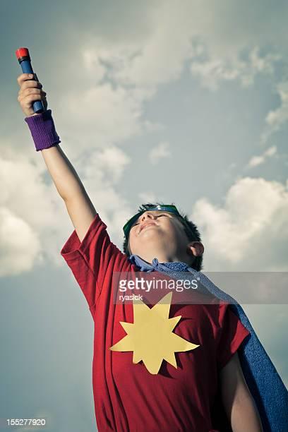 Criança vestida como super-herói em Fantasia de caseiras finge que está a voar