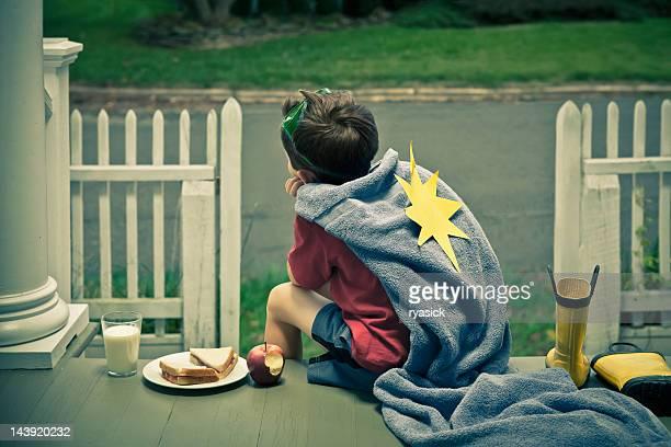 Petit garçon déguisé en super héros se trouve sur un porche prenant une pause déjeuner