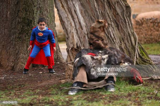 A boy dressed as Superman mocks on a masked man dressed as an 'Antruejo' carrying cowbells tied to his back taking a rest during the carnival of...