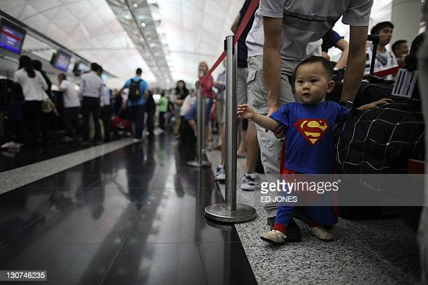 A boy dressed as superman walks between travellers waiting to check in for Qantas flights at Hong Kong's international airoprt on October 29 2011...