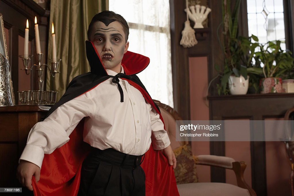 Boy (6-7) dressed as vampire posing in living room, portrait, close-up : Stock Photo