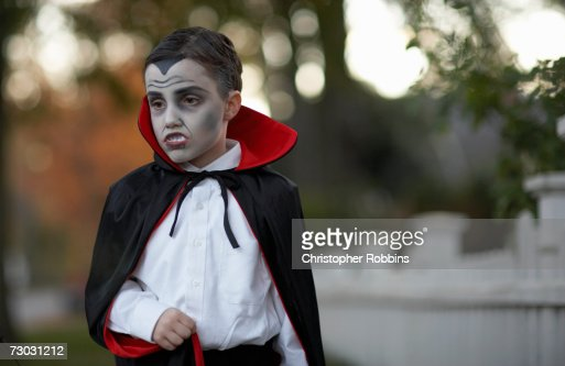 Boy (6-7) dressed as vampire standing outdoors : Stock Photo