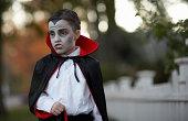 Boy (6-7) dressed as vampire standing outdoors
