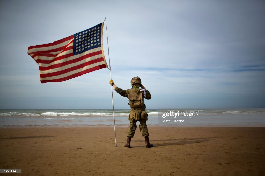 A boy dressed as World War II American soldier holds the flag of USA as he pays his respect in the Omaha Beach June 6, 2014 near Vierville-sur-Mer, France. Friday 6th June is the 70th anniversary of the D-Day landings which saw 156,000 troops from the allied countries including the United Kingdom and the United States join forces to launch an audacious attack on the beaches of Normandy, these assaults are credited with the eventual defeat of Nazi Germany. A series of events commemorating the 70th anniversary are planned for the week with many heads of state travelling to the famous beaches to pay their respects to those who lost their lives.
