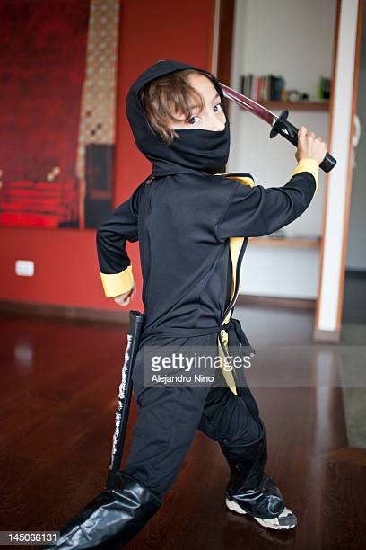 A boy dressed in a ninja costume swinging a samurai sword