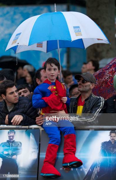 A boy dressed in a Superman costume shelters under a umbrella waiting for the actors of the film by the red carpet for the European premiere of the...