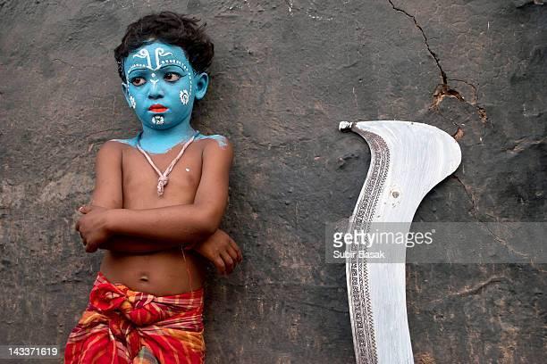 Boy dressed like krishna with sword