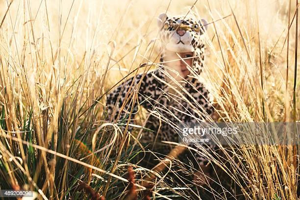 Junge verkleidet als Gepard in Tall Grass