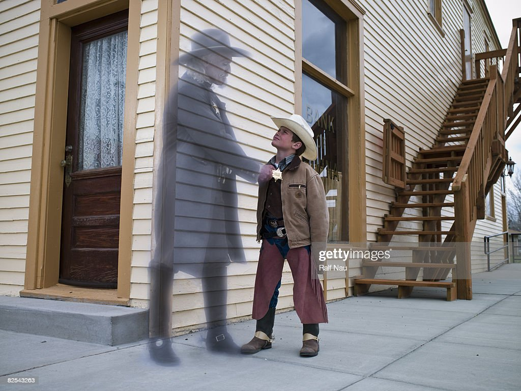 Boy dressed up as cowboy daydreaming  : Stock Photo