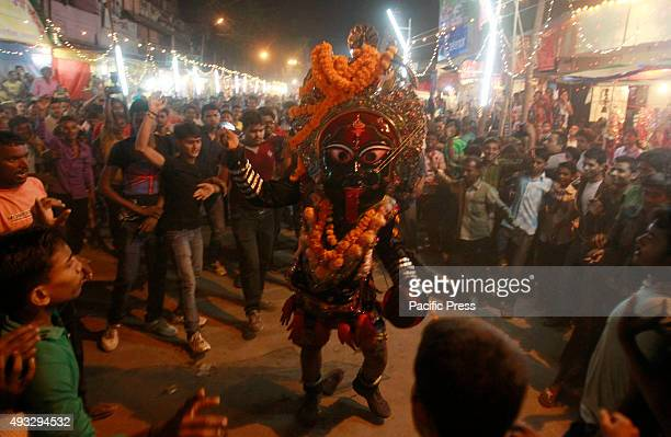 A boy dressed up as Hindu Goddess Kali perform dance during religious procession during Durga puja celebration in the northern Indian city of...