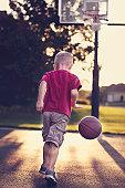 Boy dribbling basketball towards hoop