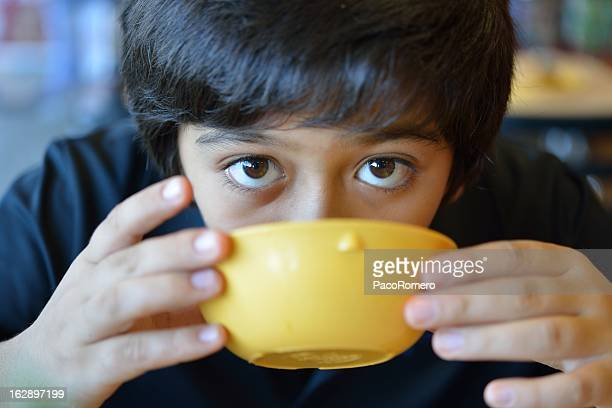 Boy drinking a bowl of soup during school lunch