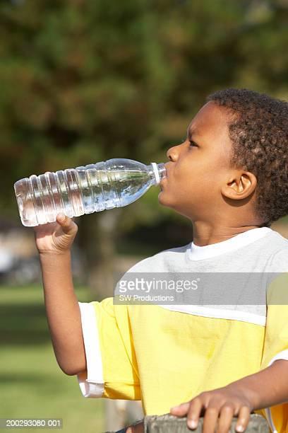 Boy (5-7) drinking from water bottle, side view