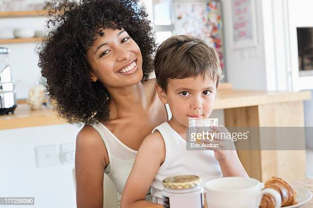 Boy drinking orange juice with his mother sitting with him