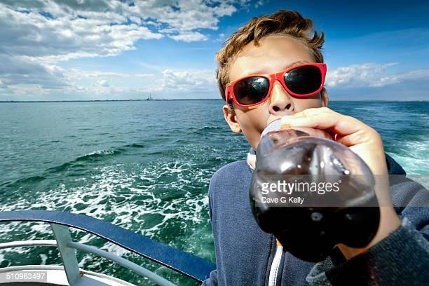 Boy Drinking Soda on Ship
