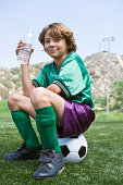 Boy drinking water and sitting on soccer ball