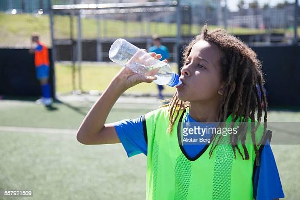 Boy drinking water at soccer training
