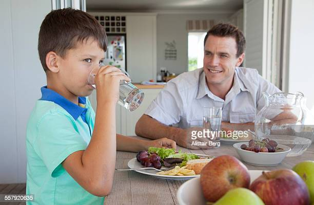 Boy drinking water at table