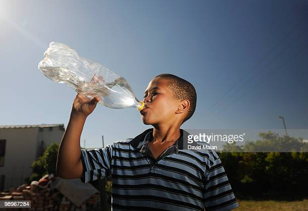 Boy (12-13) drinking water from plastic bottle, St Francis Bay, Sea Vista, Eastern Cape Province, South Africa