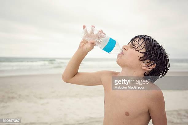Boy drinking water on beach