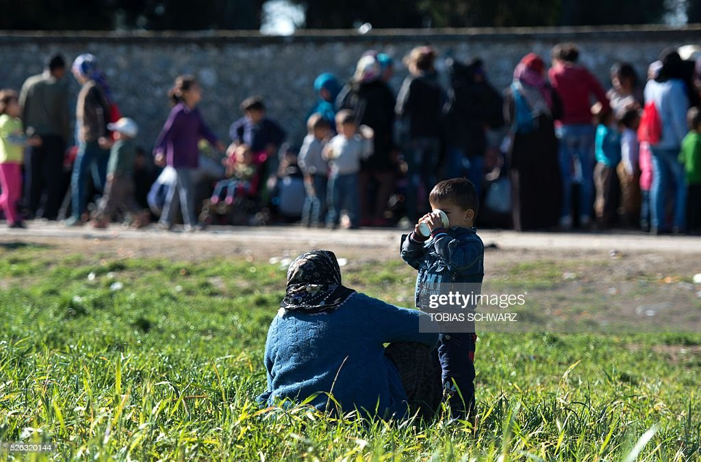 A boy drinks from a paper cup at a makeshift camp for migrants and refugees near the village of Idomeni, not far from the Greek-Macedonian border, on April 30, 2016. Some 54,000 people, many of them fleeing the war in Syria, have been stranded on Greek territory since the closure of the migrant route through the Balkans in February. / AFP / TOBIAS