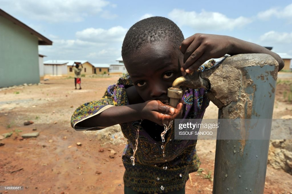 A boy drinks from a water tap in a 'new town' built by the diamond mining company Koidu Holdings, which aims to provide access to clean drinking water, education and training, free healthcare and infrastructure, in Koidu, the capital of the diamond-rich Kono district, in eastern Sierra Leone, some 250 km east from Freetown, on April 28, 2012. Small-scale artisanal mining has sustained this area since diamonds were discovered in 1930, and it was here that the 968.9-carat Star of Sierra Leone was found in 1972 -- the largest alluvial diamond ever found. Koidu also suffered some of the worst ravages of Sierra Leone's war in the nineties as rebels forced citizens to mine at gunpoint. But surface diamonds are near-depleted and only capital-intensive mining can reach the gems. On the other side of town, Koidu Holdings, a mining company owned by Israeli diamond magnate Beny Steinmetz, is testing a new plant built to process the diamonds from its two vertical kimberlite mines as part of a $150 million (115 million euro) expansion plan.