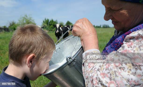 A boy drinks milk in the village of Zhadeny some 300 km southwest of Minsk on June 4 2017 A spat between Russia and Belarus seems to have spilt over...