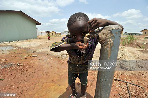 A boy drinks water from a tap on April 282012 in a 'new town' built by Koidu Holdings that provides access to clean drinking water education and...