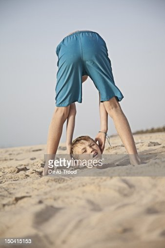 Boy drops his head on the beach in Dubai : Stock Photo