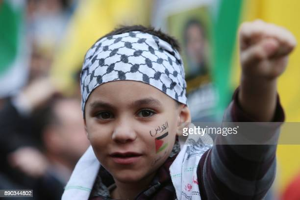 A boy earing the national Palestinian chequerred keffiyeh head dress with a Palestinian flag painted on his face with the Arabic name for Jerusalem...