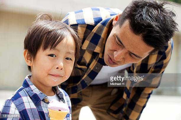 Boy eat ice with his father