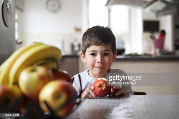A boy eating an apple in the kitchen