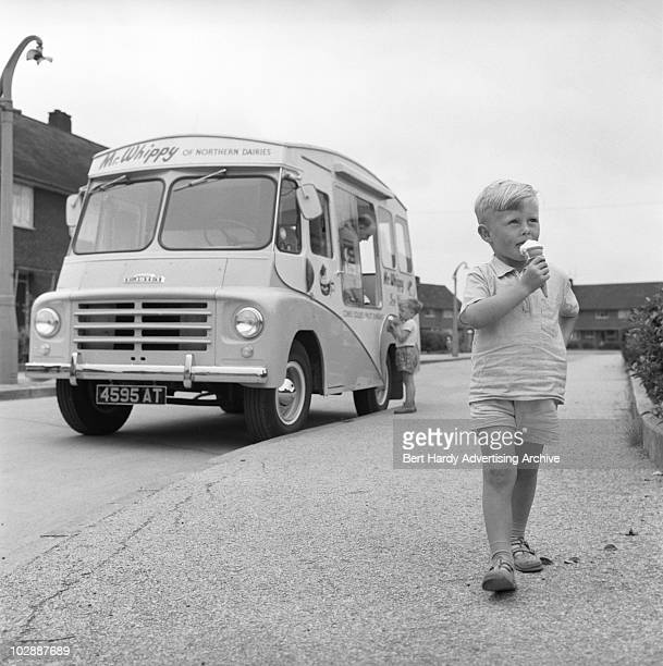 A boy eating an icecream bought from an Austin ice cream van Hull 20th July 1961