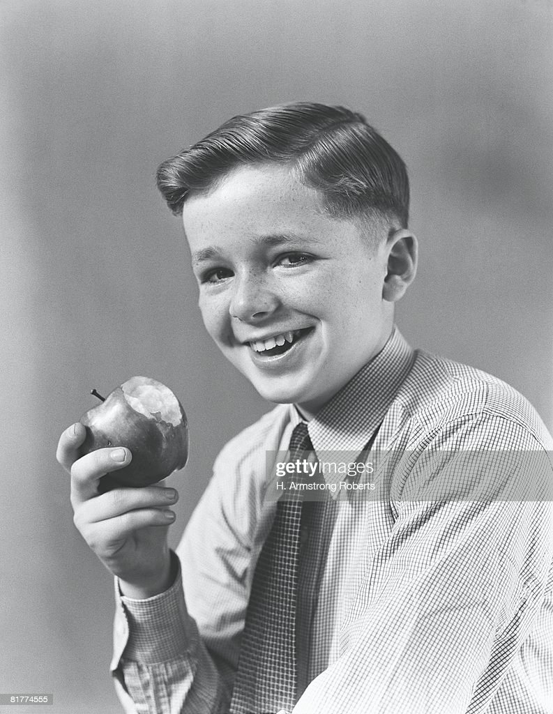 Boy eating apple, smiling, portrait. : Stock Photo