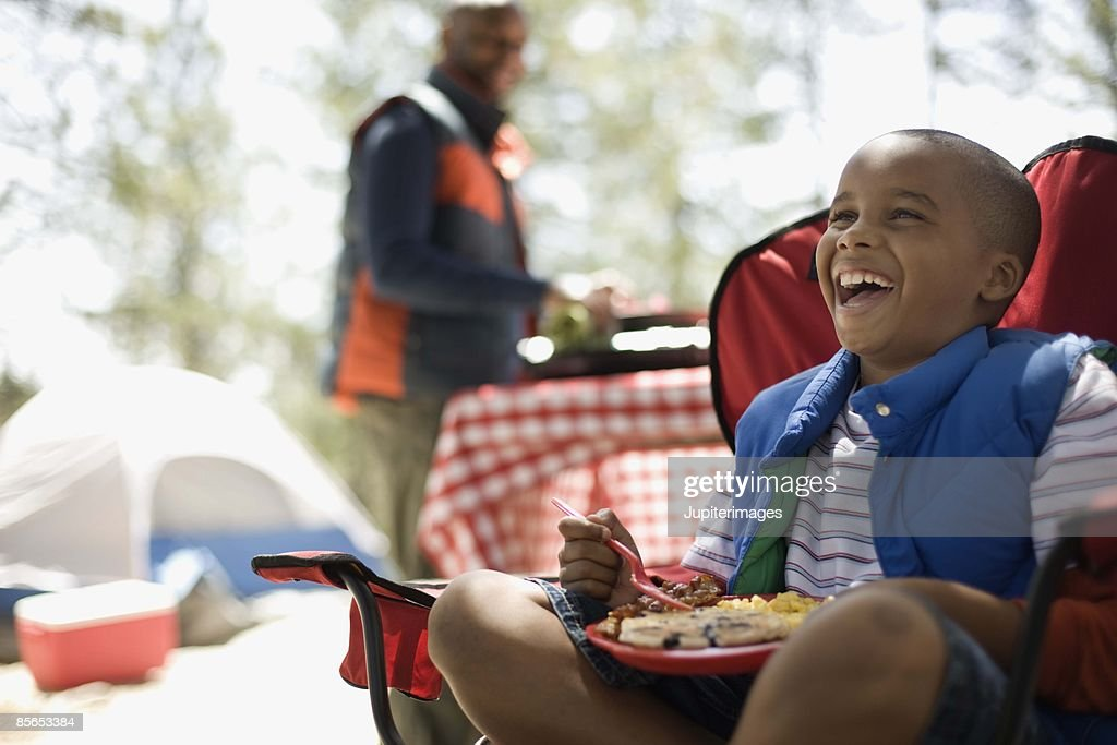 Boy eating at campsite : Stock Photo